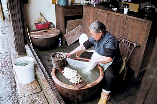 Senior woman dyeing silk cloth, Wu Town, Tongxiang City, Zhejiang Province, People's Republic of China, : Stock Photo