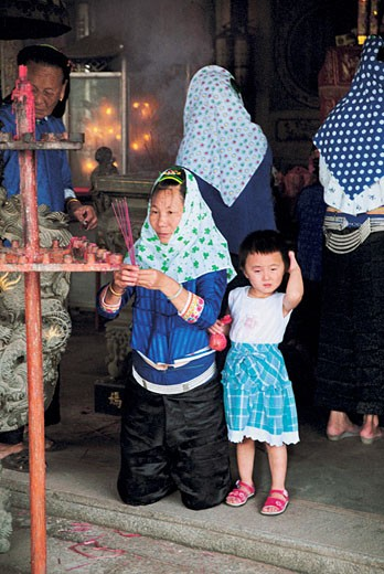 Woman with child Praying in Temple, Chongwu Town, Huian County, Fujian Province, People's Republic of China, : Stock Photo