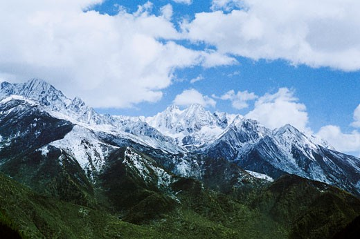 View of snow-covered mountains against cloudy sky, Mugecuo , Kangding County, Ganzi State, Sichuan Province of People's Republic of China : Stock Photo