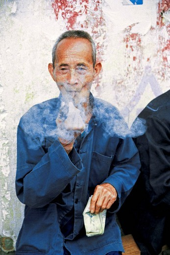 Old man smoking pipe, Yangshuo County, Guilin City, Guangxi Zhuang Nationality Autonomous Region of People's Republic of China, : Stock Photo