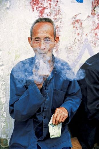Stock Photo: 1787R-3389 Old man smoking pipe, Yangshuo County, Guilin City, Guangxi Zhuang Nationality Autonomous Region of People's Republic of China,