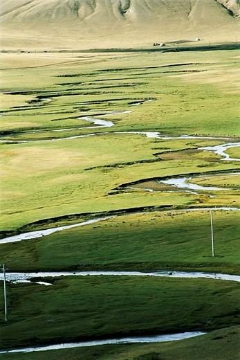 Elevated view of meandering stream passing through grassland, Bayangaole Prairie, Keshiketengqi, Chifeng City, Inner Mongolia Autonomous Region of People's Republic of China : Stock Photo