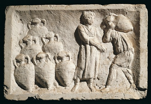 Relief depicting people carrying amphorae in wine cellar : Stock Photo