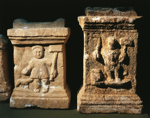 Two small altars with bas-reliefs depicting the Gallic God Sucellus holding an olla in one hand and a wooden mallet in the other : Stock Photo