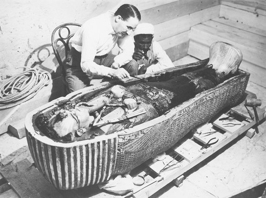 Stock Photo: 1788-23584 Egypt, Valley of the Kings, The discovery of the tomb of Pharaoh Tutankhamun (or Tutankhamen, circa 1340-1323 B.C., archaeologist Howard Carter (1874-1939) examining the third mummy-shaped sarcophagus, 1922, vintage photograph