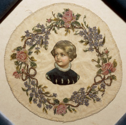 Stock Photo: 1788-26751 Embroidery, 19th century. Silk crown, embroidered in small stitch on tulle, with roses and forget-me-not and central paper figure of a child.