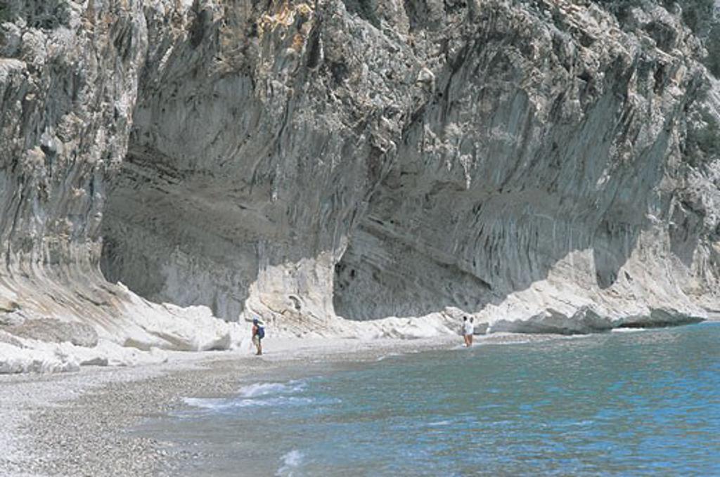 Three tourists standing on the beach, Cala Luna, Gennargentu National Park, Gulf Of Orosei, Sardinia, Italy : Stock Photo
