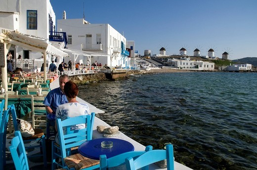 Greece, Cyclades, Mykonos Island, Former district of Alefkandra, nicknamed Little Venice, white and coloured houses on the sea, Cafe and restaurant terrace, five grinders Kato Mili in the background : Stock Photo