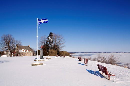 Canada, Quebec Province, Chemin du Roy, Deschambault, the old presbytery and partly frozen banks of Saint Lawrence River, Quebecois flag : Stock Photo