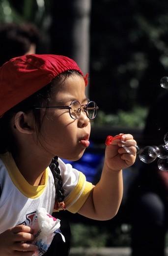 China, Hong Kong, Hong Kong Park, child blowing bubbles soap : Stock Photo