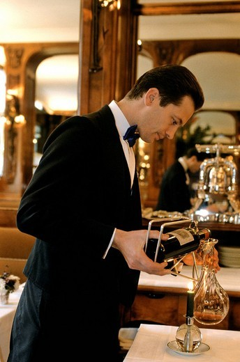 France, Paris, Place de la Madeleine, Lucas Carton restaurant, a sommelier that is decanting a bottle : Stock Photo