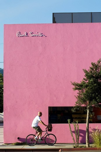 United States, California, Los Angeles, West Hollywood, Melrose Avenue, cyclist in front of Paul Smith shop : Stock Photo