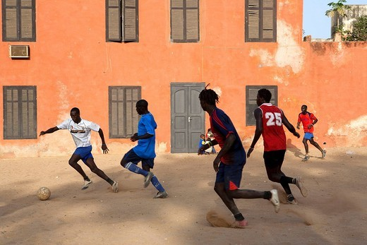 Senegal, Goree Island listed as World Heritage by UNESCO, young people playing footablle in the centre of the village : Stock Photo