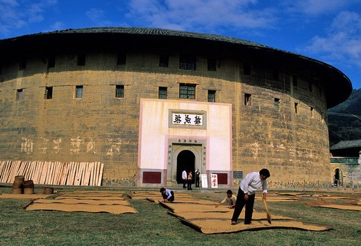 Stock Photo: 1792-118397 China, Fujian Province, Hukeng, a Tulou, building communal living structures designed to be easily defensible, made of brick, stone, or rammed earth, built by Hakka people, the rice is drying on mats