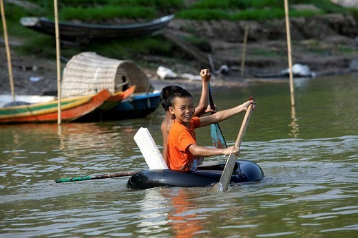 Laos, Luang Prabang province, alongside the Mekong, child playing with a buoy : Stock Photo