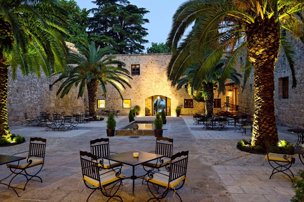 Spain, Extremadura, Jarandilla de la Vera, medieval castle of the 15th century was the home of Carlos V and transformed now into a Parador of Tourism, patio under the palms : Stock Photo