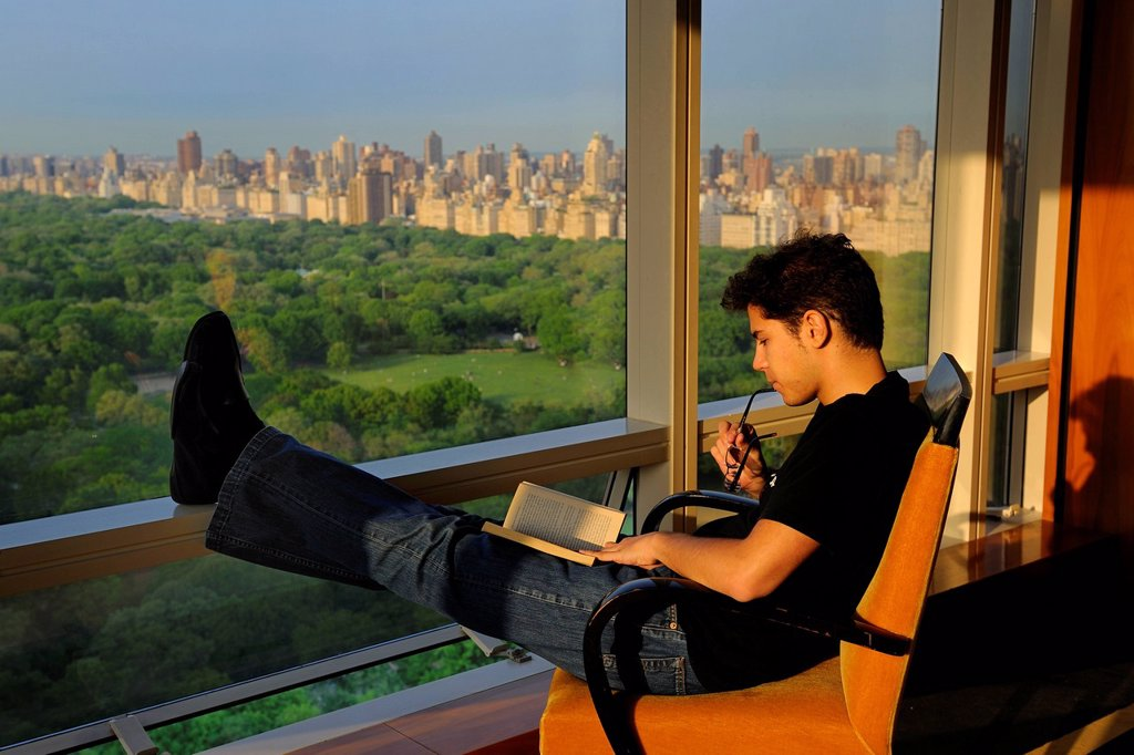 Stock Photo: 1792-130453 United States, New York City, Manhattan, reading a book facing Central Park