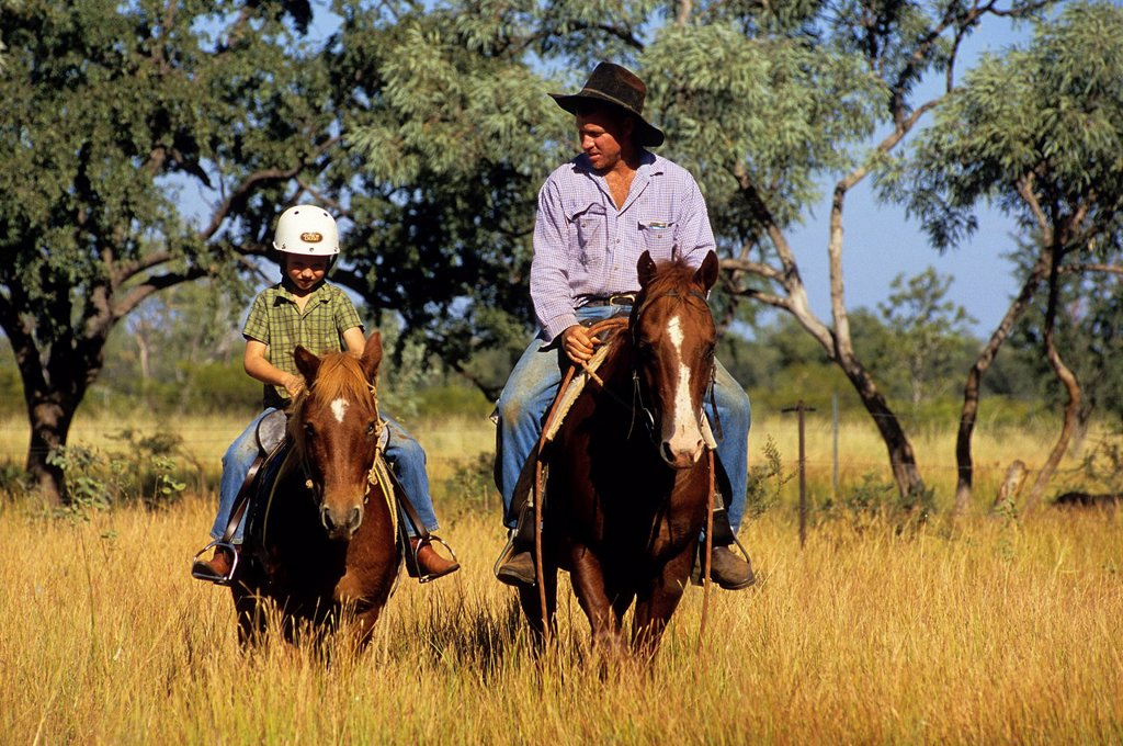 Australia, Western Australia, Kimberley Region, Mornington Wildlife Sanctuary, Bluey Cook and his son David on horses : Stock Photo