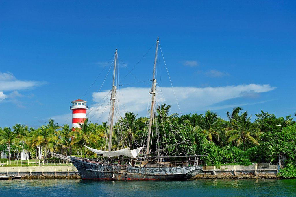 Bahamas, Grand Bahama Island, Freeport, Port Lucaya, Ghost, boat of Pirates of the Caribbean movie with a lighthouse in background : Stock Photo
