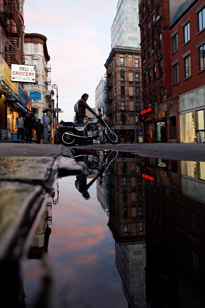 United States, New York City, Manhattan, East Village, reflection of a motorcyclist in a puddle : Stock Photo