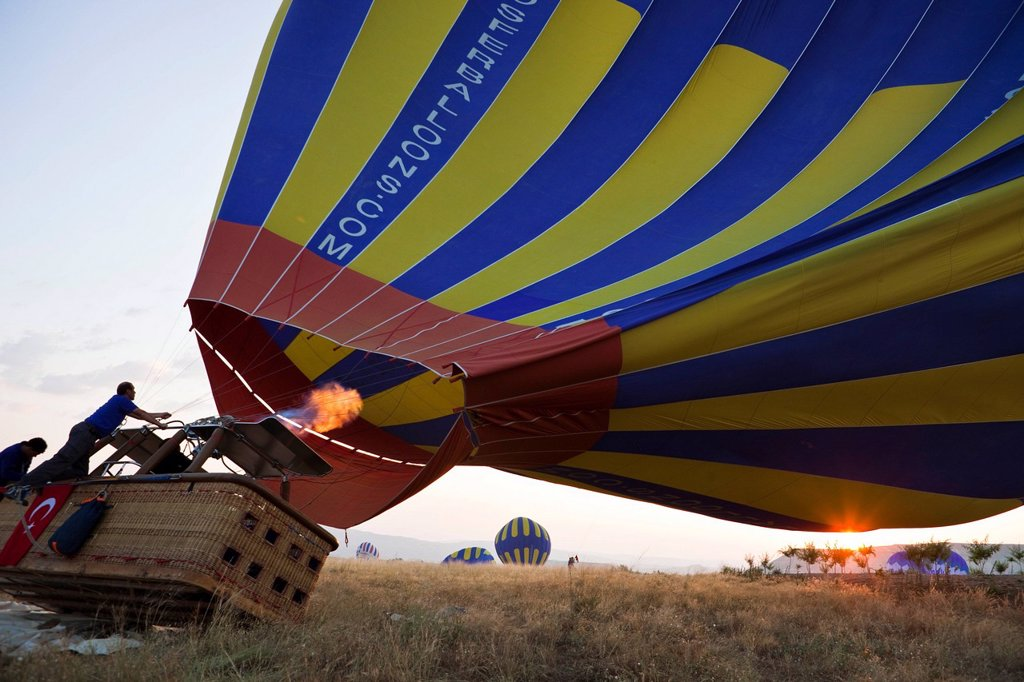 Turkey, Central Anatolia, Cappadocia, listed as World Heritage by UNESCO, Goreme valley, inflating the balloon : Stock Photo
