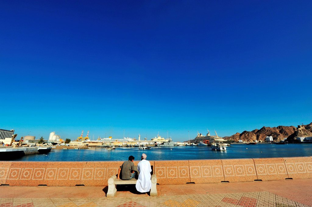 Sultanate of Oman, Muscat, Muttrah port area, Omani men sitting on a public bench on the Corniche : Stock Photo