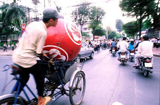 Vietnam, Saigon Ho Chi Minh City, a boy carrying a ball for the dragon dance on his bicycle through the traffic jams : Stock Photo