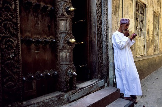 Stock Photo: 1792-88320 Tanzania, Zanzibar Archipelago, Unguja island Zanzibar, town of Zanzibar, Stone Town district, listed as World Heritage by UNESCO, Sultan J Mugheiry, an old Zanzibarite seaman taking a stroll in front of the famous sculpted wooden door in Sokomuogo street