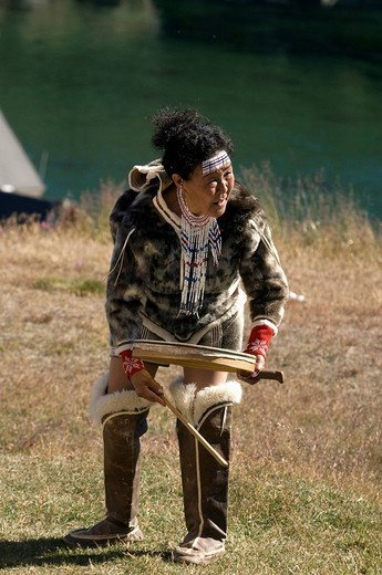 Greenland, East coast, Angmassalik region, Sermilik fjord, Tasiilaq, Inuit woman in traditional costume playing the tambourine dancing and chanting Inuit songs : Stock Photo
