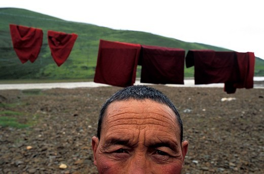 China, Sichuan province, on the high plains, a monk standing in front of his drying robes : Stock Photo