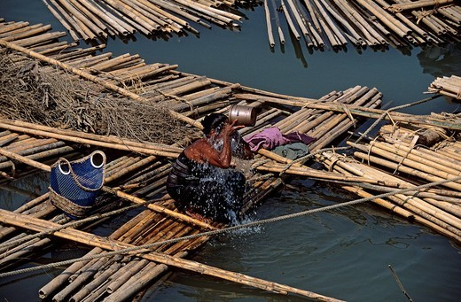 Myanmar Burma, Mandalay Division, nearby Mandalay, Burmese people live in precarious home on floating wood which they bring from the North to the delta of Irrawaddy River : Stock Photo