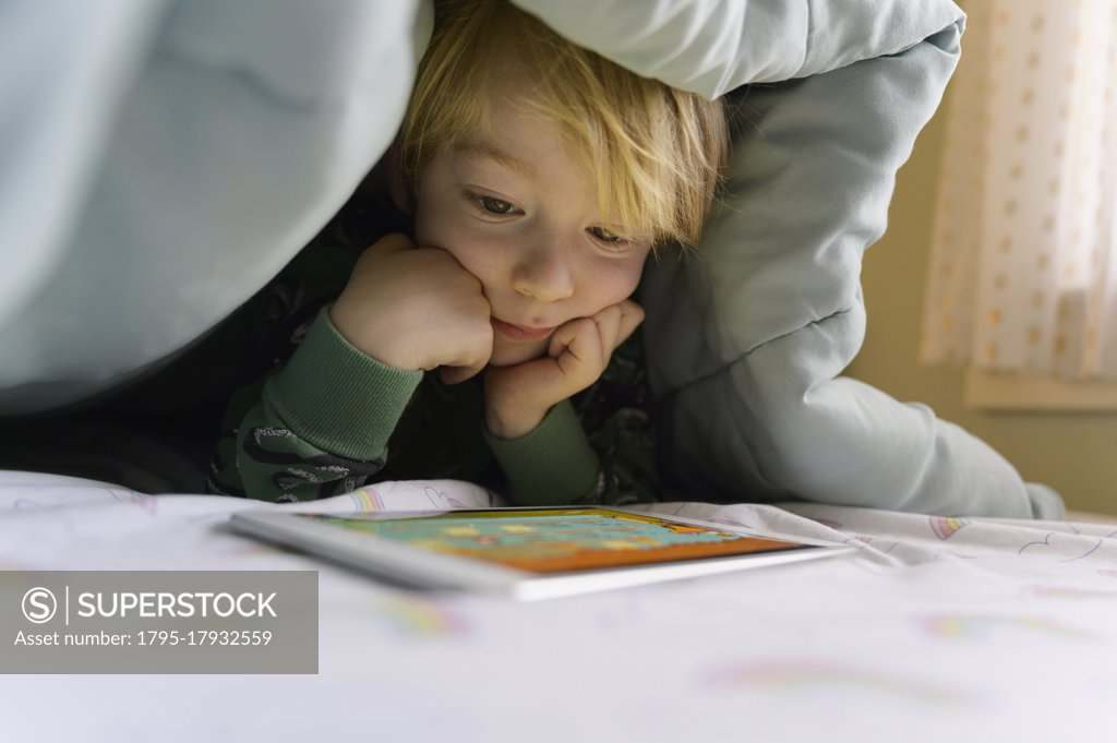 Stock Photo: 1795-17932559 Boy (6-7) on bed looking at digital tablet