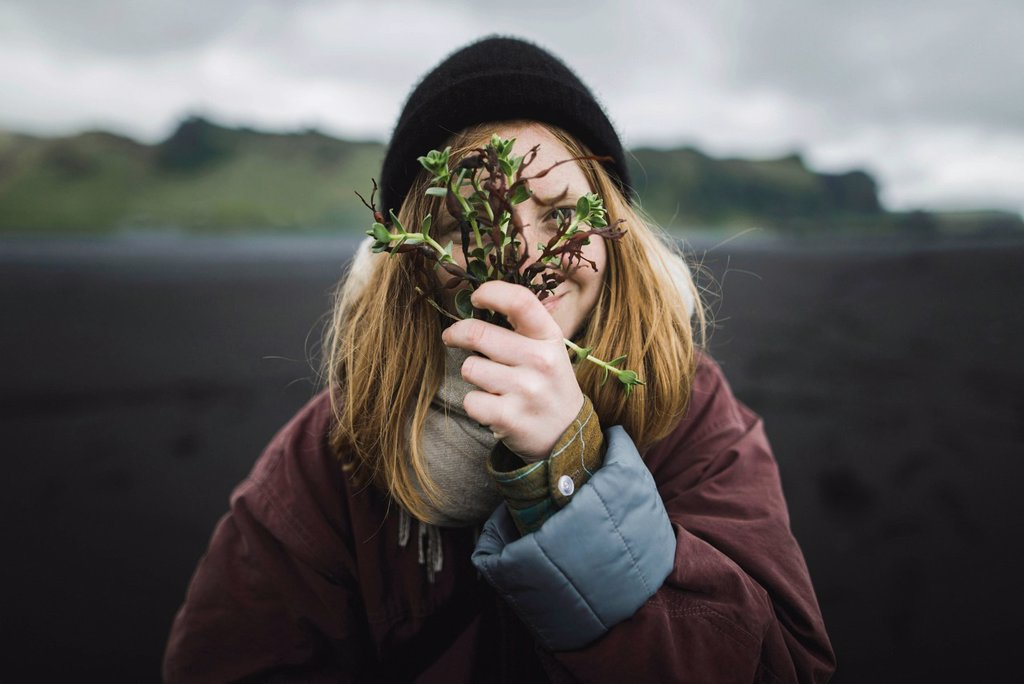 Stock Photo: 1795-111462595 Woman holding plants over her face on beach