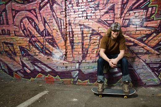 Young man with skateboard in front of graffitied wall : Stock Photo