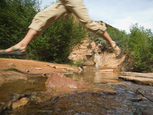 Woman jumping over stream : Stock Photo