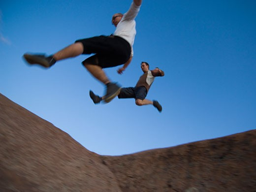 Stock Photo: 1795R-11372 Men jumping over rock formations