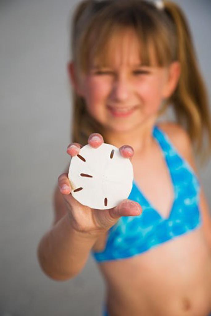 Stock Photo: 1795R-11980 Girl holding up sand dollar, Florida, United States
