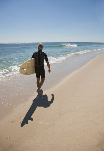 Man carrying surfboard at beach : Stock Photo