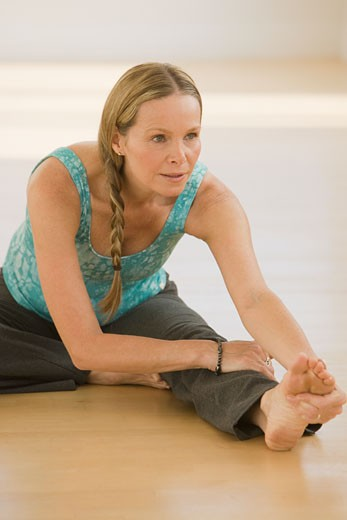 Stock Photo: 1795R-12210 Woman stretching on floor