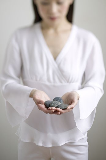 Young woman holding stones : Stock Photo