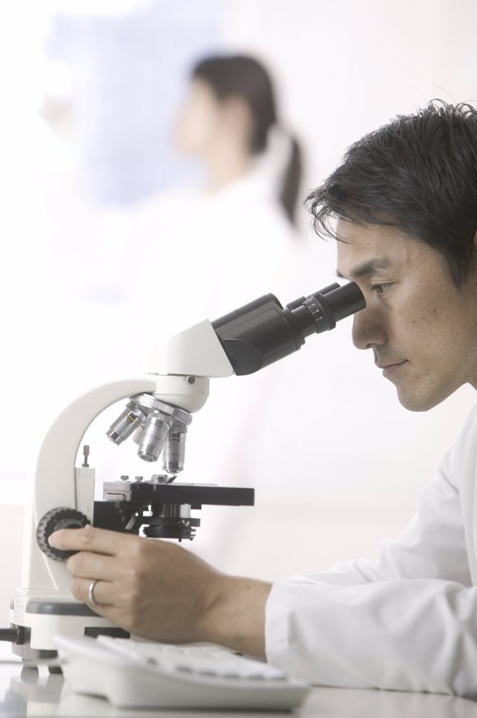 Scientist looking in microscope : Stock Photo
