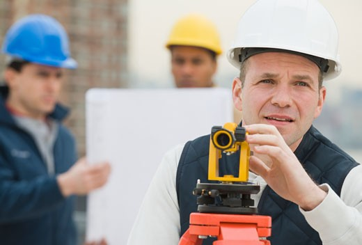 Male surveyor looking through measuring device : Stock Photo