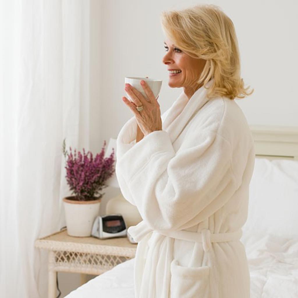 Senior woman in bathrobe drinking coffee : Stock Photo