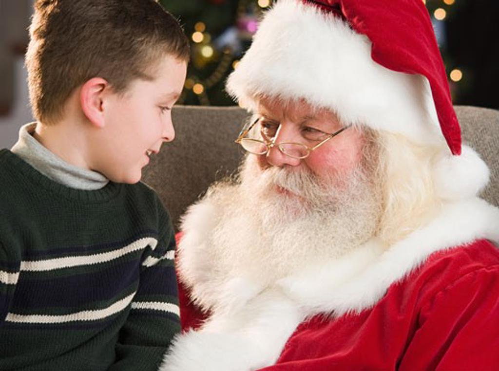 Boy sitting on Santa Claus's lap : Stock Photo