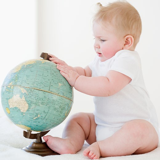 Baby looking at globe : Stock Photo
