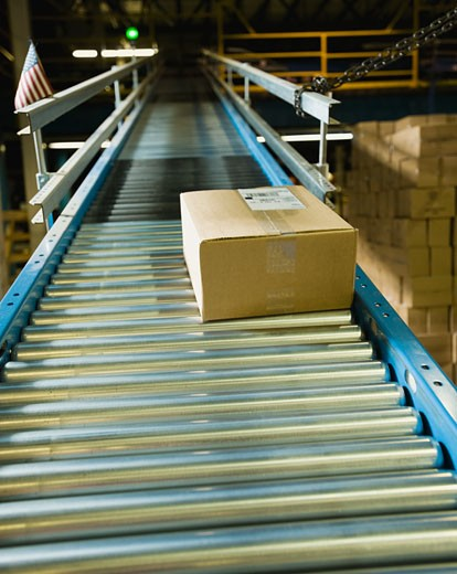 Package on conveyor belt in warehouse : Stock Photo