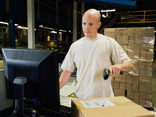 Warehouse worker scanning package : Stock Photo