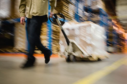 Warehouse worker pulling palette : Stock Photo