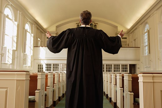 Priest with arms raised in church : Stock Photo