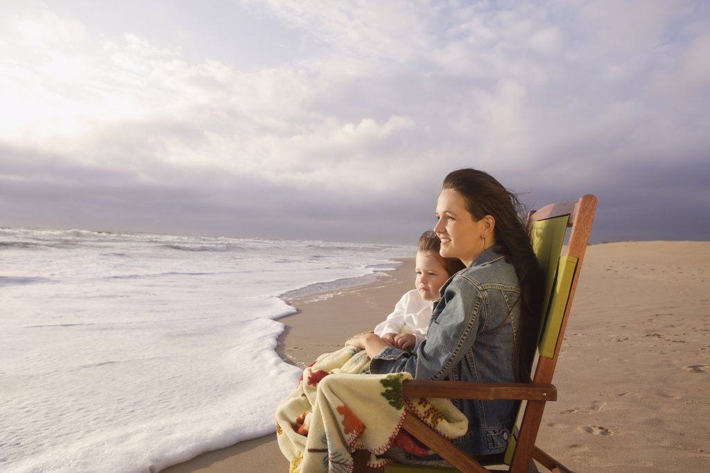 Mother and child sitting in beach chair : Stock Photo